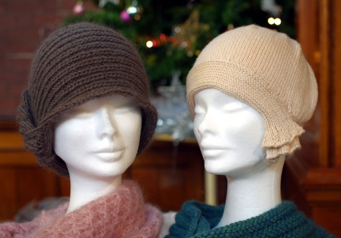 Brown hat with cable down one side, cream 1920s style hat and dark green snood